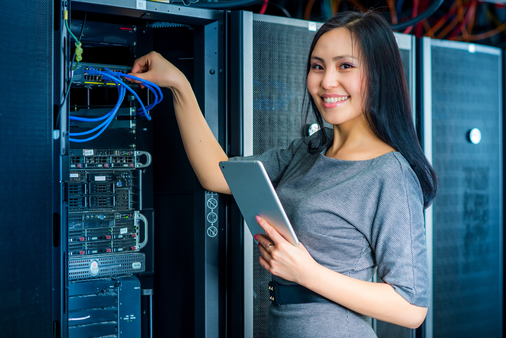 Young,Engineer,Businesswoman,With,Tablet,In,Network,Server,Room
